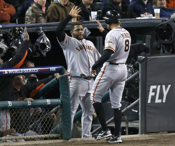 San Francisco Giants' Hunter Pence is welcomed back to the dugout by teammate Pablo Sandoval after scoring in the second inning against the Detroit Tigers during Game 4 of the MLB World Series baseball championship in Detroit, Michigan, October 28, 2012.