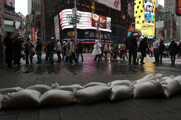 People walk by sand bags in Times Square as Hurricane Sandy begins to affect New York City.