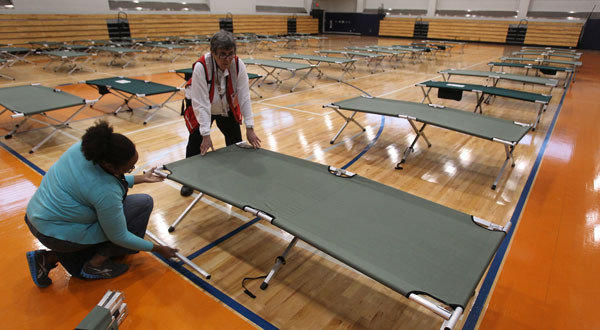 American Red Cross workers set up cots inside the West Philadelphia High School in Philadelphia.