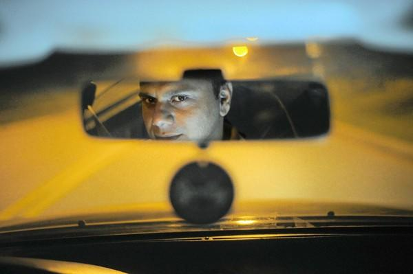 Pizza delivery driver Muhammad Shakeel Anjum is reflected in his rear view mirror while working his night job delivering food for a pizza restaurant.