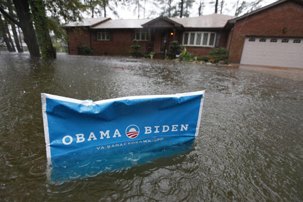 An Obama campaign sign rises above the floodwaters in front of a home as rain falls in Norfolk, Va.