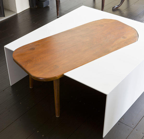 A wood table with sentimental value was made more functional with a modern metal extension. the contrasting style of the metal planes accentuates the character of the wood piece.