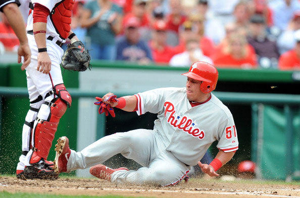Carlos Ruiz of the Philadelphia Phillies slides into home plate and scores in the fourth inning against the Washington Nationals on October 3, 2012 in Washington, DC.