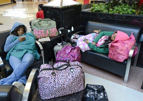 Thanks to Hurricane Sandy, Baltimore-bound travelers Nene Coleman, left, and Shan Dora are stranded at Hartsfield-Jackson Atlanta International Airport. Coleman said Monday that the airline might not be able to get them home until Nov. 1.