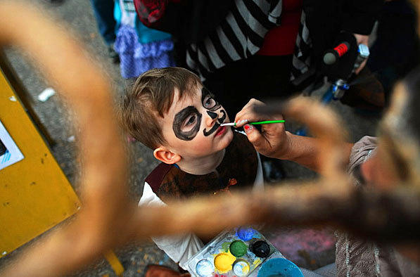 A little boy preps for a Halloween parade in Baltimore. Once an ancient Celtic pagan rite held to celebrate the dead, Halloween is primarily a children's event that gives adults an excuse to dress up and act like kids.