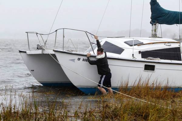 Photos: Hurricane Sandy: A man struggles to secure his boat near a marsh after breaking off its mooring and beaching itself during the effects of Hurricane Sandy in Quincy, Massachusetts. The monster storm bearing down on the East Coast, strengthened on Monday after hundreds of thousands moved to higher ground.