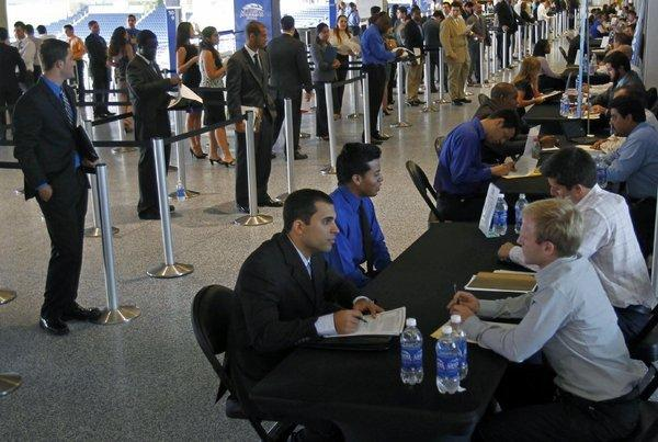 Job applicants are interviewed by Miami Marlins staff in Miami last week. The Labor Department said it was hopeful Hurricane Sandy would not delay Friday's October unemployment report.