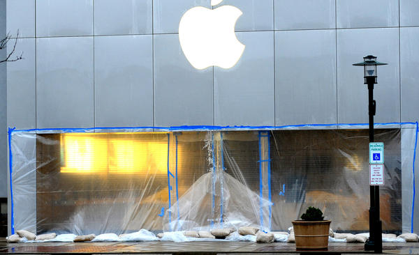 The Apple Store in Whitehall is closed and covered in plastic that is sandbagged down in high winds and rain from the storm known as Sandy Monday.