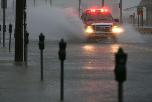 An emergency vehicle drives down an avenue flooded by Hurricane Sandy on Oct. 29 in Cape May, N.J.