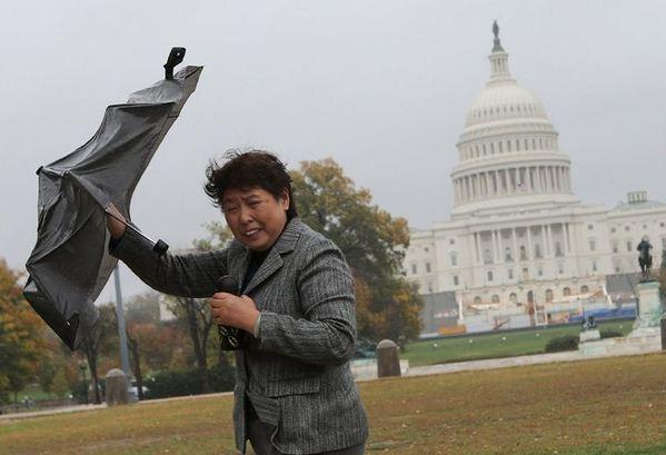 A tourist struggles against gusting winds as the leading edge of Hurricane Sandy moves across the nation's capital on Monday.
