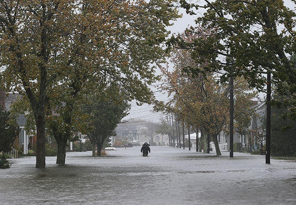 A lone figure makes his way down 7th Street as high tide, rain and winds flood local streets on October 29, 2012 in Lindenhurst, New York. The storm, which threatens 50 million people in the eastern third of the U.S., is expected to bring days of rain, high winds and possibly heavy snow.