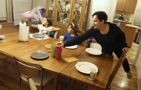 """Lyla, left, 10, Julia, 6, and mom Michelle Stern get ready for family dinner at their Northwest Side home. The Sterns try to schedule the children's after-school activities on the same days to leave time for family meals. """"The biggest thing we have done is to be as consistent as possible,"""" dad Dave says."""