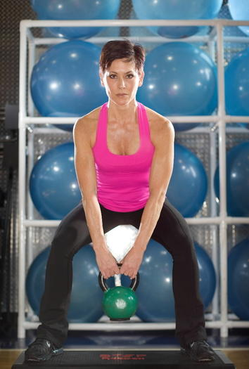 Group fitness trainer Sarah Ruhl demonstrates how to lift a kettlebell at the Lincoln Park Athletic Club where she works in Chicago.