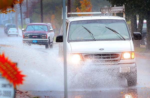 A van splashes its way down North Allison Street in Greencastle, Pa., Monday as Hurricane Sandy started to drop rain in the Tri-State area.