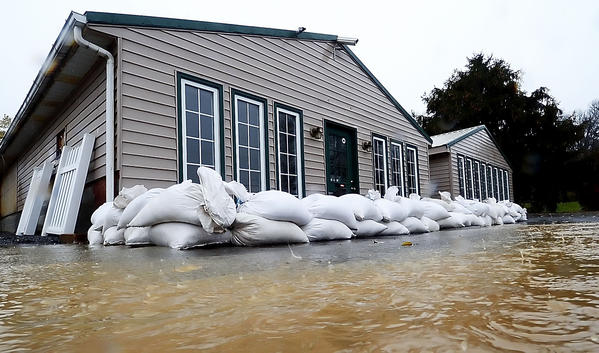 Sandbags protect the entrance to a business on Lappans Road Monday as the parking lot fills with water.