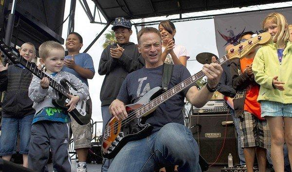 Gary Sinise with his Lt. Dan Band shows off his bass playing to Andrew James Bretzman, 3, after inviting children onto the stage.