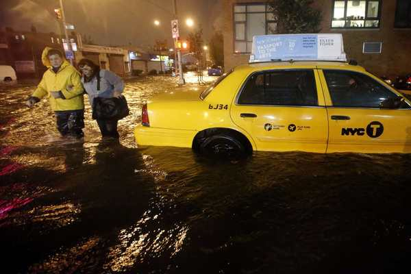 Photos: Hurricane Sandy: Pedestrians walk past a submerged taxi in Brooklyn, New York, as Hurricane Sandy made landfall in the northeastern United States. Hurricane Sandy began battering the U.S. East Coast on Monday with fierce winds and driving rain, as the monster storm shut down transportation, shuttered businesses and sent thousands scrambling for higher ground hours before the worst was due to strike.
