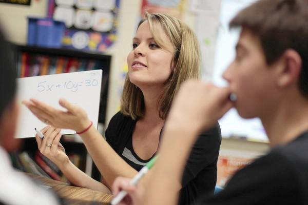 Math teacher Breann Cooper works with a small group Friday reviewing concepts during an Algebra I class for middle-schoolers at Lincoln Prairie School in Hoffman Estates. The performance of algebra students in seventh- and eighth-grade will take on new significance next year.