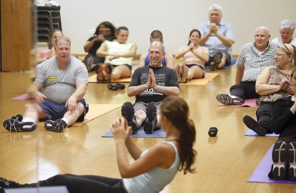 Dr. John Principe, center, takes a fitness class with his patients at WellBeingMD Ltd. in Palos Heights. He regularly suggests fitness regimens, such as this class taught by Agne Doniela, foreground, and dietary changes for his patients.