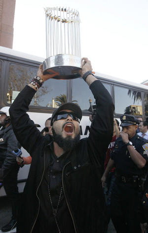 San Francisco Giants' Sergio Romo yells as he carries the World Series trophy Monday outside of AT&T Park in San Francisco.