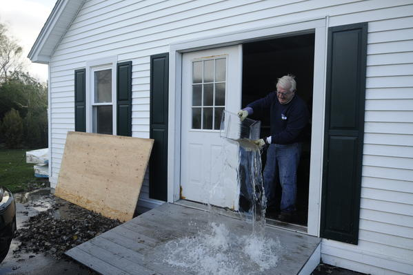 Dominique Brault of Old Lyme dumps water out of a refrigerator drawer while helping clean up water damage at his brother-in-law's Sea Lane home in the Indiantown Beach neighborhood in Old Saybrook Tuesday, the day after Hurricane Sandy flooded the area with 4 feet of water.