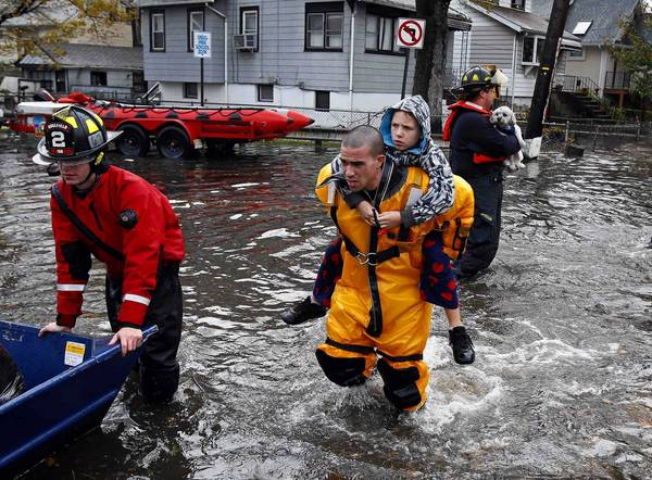 A rescue worker carries a boy on his back as emergency personnel rescue residents from flood waters brought on by Hurricane Sandy in Little Ferry, New Jersey.
