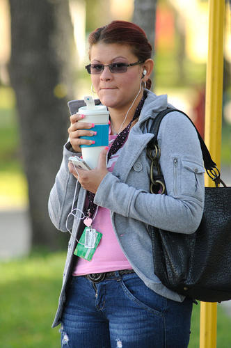 Elsie Macias keeps warm with her hot coffee as she waits to catch the bus to school.   Cool weather will continue with temperatures dipping into the low 50's this evening.