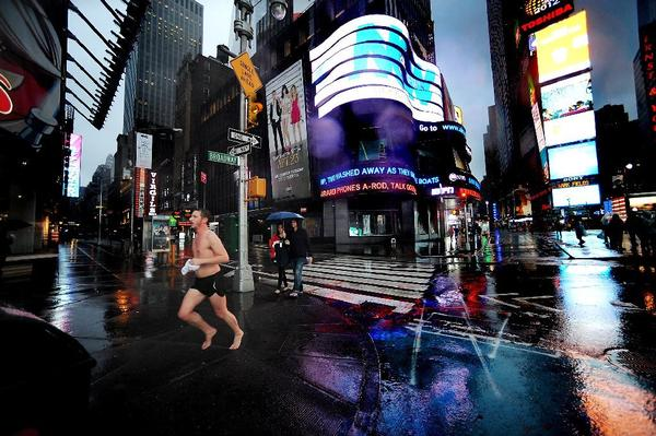 One jogger does not mind the inclement weather in the Times Square area of New York City on Monday afternoon as the city prepared for Hurricane Sandy. Few people drove, which so far has helped the region deal with lost fuel supplies from refinery closures.