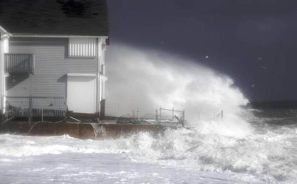 Waves crash against the shoreline during high tide in Milford, Connecticut.