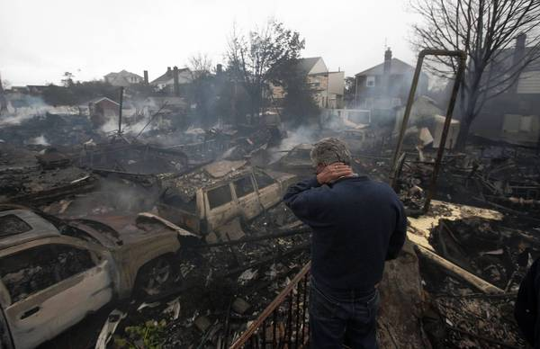 A resident looks over the remains of burned homes in the Breezy Point neighborhood of New York.