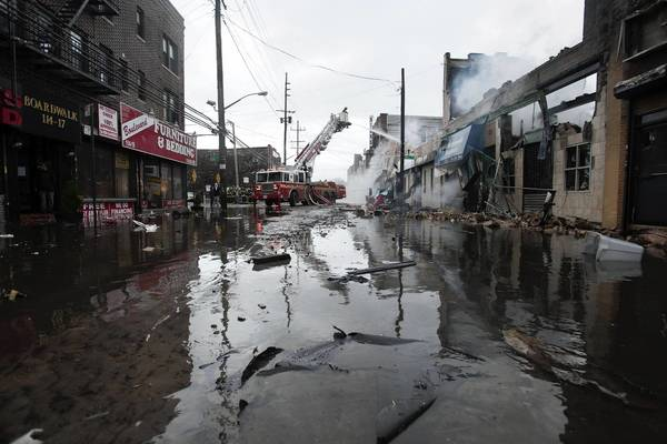 Photos: Hurricane Sandy: Firefighters work to extinguish a fire on a flooded street in the Rockaway section of New York.