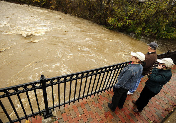 Bonnie Marshall, left, stood with her friends, Ed and Sandy Lohmeyer, of Ellicott City, on the Ellicott City Bridge over the Patapsco after high winds and rain from Sandy drenched the area on Monday night.