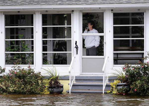 Photos: Hurricane Sandy: Maryann Schmitt talks on the phone in her house in the aftermath of Hurricane Sandy in South Bethany Beach, Delaware. Schmitt and her husband chose not to ride out the storm in their house, and returned the day after to find only their garage was underwater.