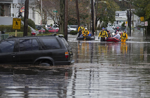 People are rescued by boat on a flooded street in Little Ferry, N.J., in the wake of Hurricane Sandy.