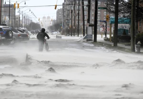 A resident walks down a street covered in beach sand due to wind and flooding from Hurricane Sandy in Long Beach, New York. The storm has claimed at least 33 lives and has caused massive flooding across much of the Atlantic seaboard.