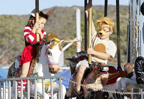 Thomas Gonzales, 5, right, dressed as a lion, and Mai Kramer, 5, hold tight as they ride on a mini merry-go-round during the annual Boo Blast Halloween Carnival at El Morro Elementary School on Friday.