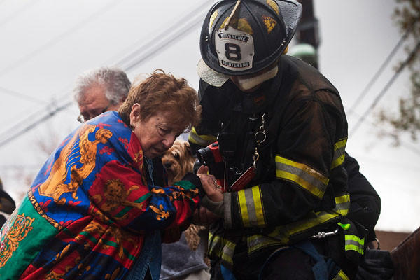 A woman is helped from a truck by a firefighter after being evacuated in New Jersey.