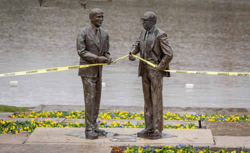 Caution tape is partially held up by the Rouse statues at Lakefront warning people that the end of the landing and part of dock are submerged by storm waters.