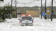 A Port Authority Police SUV makes its way through flood waters covering roads leading toward Teterboro Airport in Teterboro