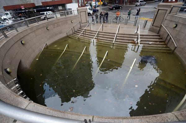 People take photos at water filling the Bowling Green subway station in Battery Park in New York on Tuesday as New Yorkers cope with the aftermath of Hurricane Sandy.