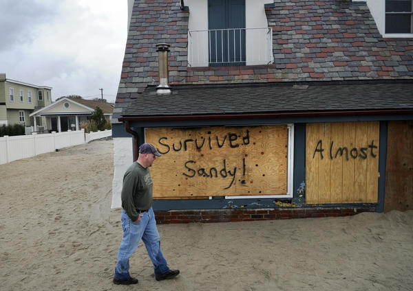 "Christopher Harding of Wethersfield walks around his family's beachfront home at White Sands Beach Tuesday. Although the house is intact, more than 6 feet of water traveled trough the house and filled it with sand so it ""almost"" survived."