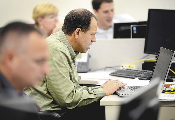 Jim Painter, center, manager of engineering services for Potomac Edison, worked Tuesday as a coordinator at the utility's hazard dispatch center on Bower Avenue in Halfway.