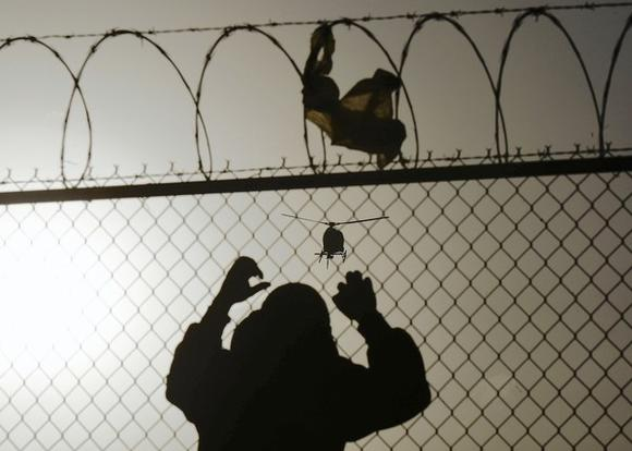A man watches a U.S. border patrol helicopter from a fence at the border between Mexico and the United States, in Ciudad Juarez
