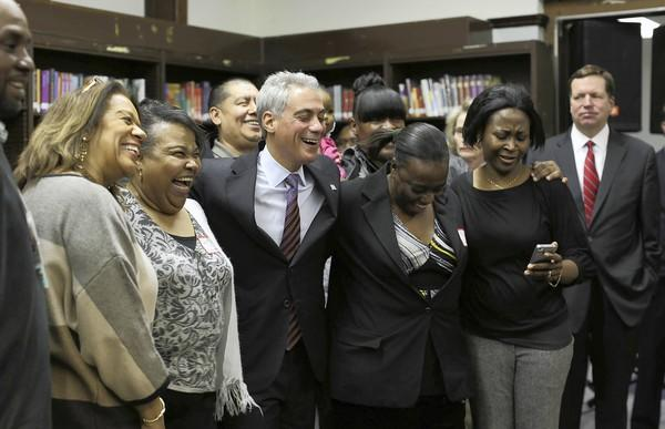 Mayor Rahm Emanuel, center, and schools CEO Barbara Byrd-Bennett, far left, pose for pictures Tuesday with parents at Eugene Field Elementary School, 7019 N. Ashland Ave., after a news conference announcing parents at 70 CPS schools will be eligible for $25 Walgreens cards for picking up student report cards and attending a conference with their child's teacher.