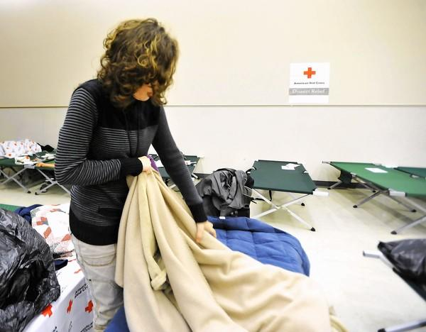 Danielle Vega straighten ups her bed area and is staying with her mother Cindy Seager (not shown) both of Bethlehem at the American Red Cross Disaster Service Area at 2121 Cityline Line Road in Bethlehem on Tuesday.