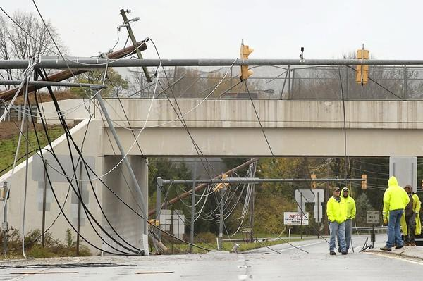A pole damaged by high winds leans near dangling wires on Rt 100, as linemen from PPL work nearby to restore electricity o near the RT 222 interchange in Upper Macungie Twp. on Tuesday, as the Lehigh Valley recovers from the damage brought on by Hurricane Sandy.