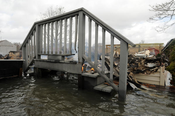 Still flaming deck stairs are all that remain standing in the smoldering ruins of a cottage on Saye Street in the Chalker Beach neighborhood of Old Saybrook. The cottage burned to the ground Monday night during Hurricane Sandy. Flooding prevented firefighters from reaching the scene.