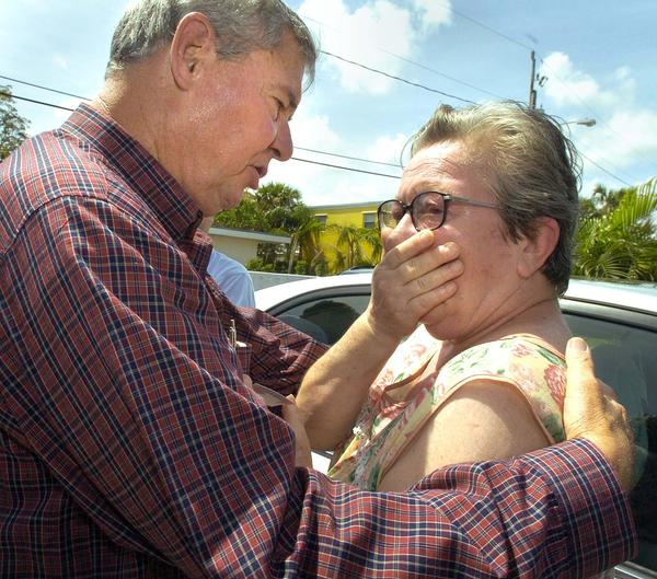 Florida Senator Bob Graham comforts Isabel Ulrich of the Pineapple Park neighborhood in West Palm Beach whos home was damaged by Hurricane Frances .During a tour of the city's hardest hit neighborhoods.
