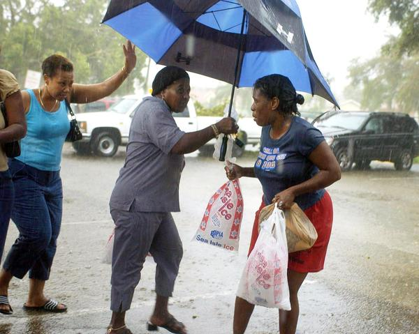 Victims of hurricane Frances who waited in line for hours walk away with bags of ice in a thunder storm during hurricane relief distribution at Pompey Park in Delray Beach.