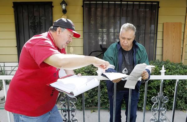 Culinary worker Santos Garcia, left, talks with resident Mario Romo last week while canvassing a North Las Vegas neighborhood. Members of powerful, heavily Latino unions are asking voters to reelect President Obama and send Rep. Shelley Berkley to the Senate.